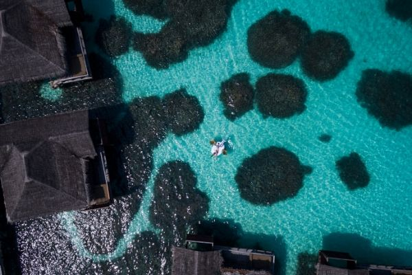 Anantara Resort, Maldives. Woman floating in the crystal clear ocean near an over-water bungaow.