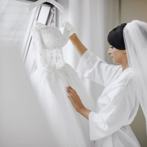 Bride hanging up her wedding dress - postponed due to COVID 19