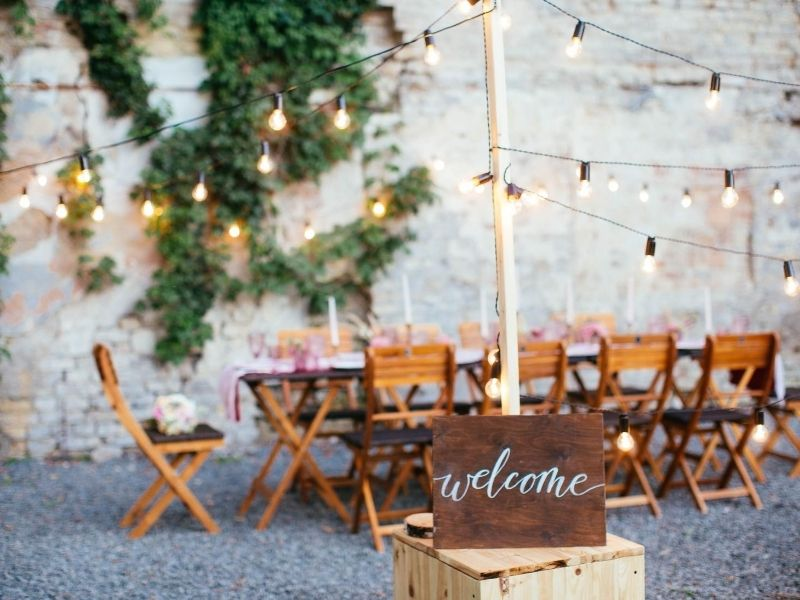 - Wooden chairs and table outside beneath faity lights. Geelong Bridal Expo March 2021